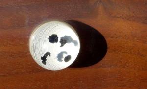 Měsíční hornina v detailu, jde o čtyři tmavé kousky velikosti několika milimetrů