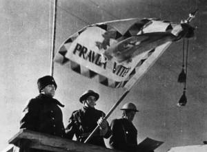 13 - Plk. Heliodor Píka předává 1. polnímu praporu bojový prapor. Vlevo H. Píka, uprostřed praporečník četař Osvald Šafařík, vpravo velitel praporu L. Svoboda.