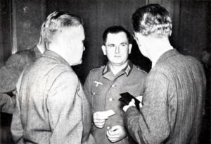 19 - Desátník Jiří Šmolík (uprostřed, v německém stejnokroji), zajatý u Sokolova a zneužitý v nacistické propagační kampani proti čs. exilu