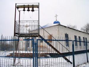 Budova nového kostela v Sokolovu už postupně začíná kostel připomínat. V popředí improvizovaná zvonice.