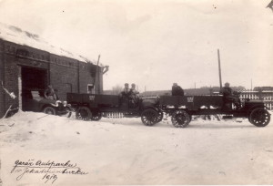 Garáž autoparku v Jekatěrinburgu v roce 1919. Vpravo dva nákladní automobily Packard. Na boku mají červenobílé označení 1. čs. autoodílu. Vlevo osobní automobil Pathfinder. Foto archiv VHÚ.