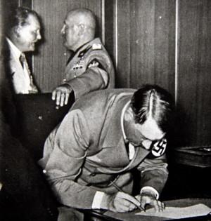 Hitler podepisuje Mnichovskou dohodu, v pozadí Göring a Mussolini. Foto sbírka VHÚ.