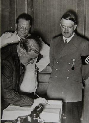 Francouzský premiér Édouard Daladier se podepisuje do pamětní knihy hostů, Hitler a Göring přihlížejí. Foto sbírka VHÚ.