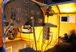 Link Trainer - letecký trenažér / Kanada 1940. V trenažéru jsou umístěny ovladače přípusti motoru,držák palubních hodin, ruční a nožní řízení, spojovací skříňka radia. Z přístrojů jsou vidět rychloměr, výškoměr, zatáčkoměr, umělý horizont, vodorovný kompas, variometr, ukazatel ILS, otáčkoměr. Na dalším záběru je ovládací stůl instruktora se záznamem letěné trasy.