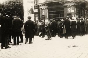 Shluk lidí před mobilizační vyhláškou, vylepenou na vývěsce před Šroubkovou restaurací na rohu Václavského náměstí v Praze, zachycuje momentka pořízená o svatoanenské neděli 26. července 1914. Foto sbírka VHÚ.