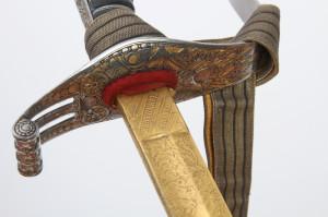 Záštitný list se zlaceným reliéfem vojenských trofejí.