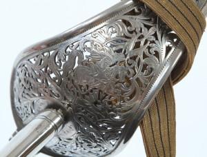 Koš je prořezáván rostlinným ornamentem a postavou svatého Jiří bojujícího s drakem.
