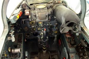 Celkový pohled do kabiny. Na obrázku je vidět sdružená páka přípustí motorů, panel přístrojů pro kontrolu letu, spodní část gyroskopického zaměřovače ASP-5 N, kaučukový tubus obrazovky radiolokátoru a panel ladění radiokompasu.