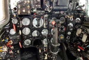 Celkový pohled na palubní desku s indikátory tlaku vzduchu a kyslíku, ovladačem podvozku a skříňkou předvolby zbraní. Svislá červená táhla jsou nouzové vysouvání podvozku a vztlakových klapek.