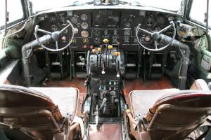Celkový pohled do pilotní kabiny se zdvojeným volantovým řízením přístroji pro kontrolu letu a motorů a středovým sloupkem, kde jsou umístěny páky ovládání korekce, přípustí, ovládání vrtulí, podvozků, klapek a autopilota. Dále se na něm nacházejí ovladače vyvážení všech kormidel, žaluzií a nouzových systémů.
