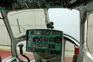 Celkový pohled na pilotní prostor s ruční řídící pákou, elektricky vyhřívaným čelním sklem, ventilátorem a panely s tably a úsekovými spínači.
