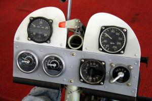 Detailní pohled na palubní desku, obsahující otáčkoměr, rychloměr, automobilový teploměr a tlakoměr oleje a variometr.