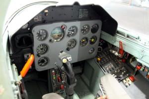 Celkový pohled ukazuje účelný a jednoduchý design kabiny žáka. Červená páka vlevo je uzavírání překrytu. Na ruční řídící páce jsou ovladače zbraní, vyvážení a brzd.