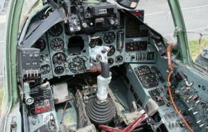 Celkový pohled do kabiny letounu s hlavními přístroji pro kontrolu letu, motorů a systémů. Uprostřed je ruční řídící páka se spínači výzbroje a vyvážení.