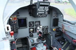 Přední pilotní kabina L-159 T1 je opravdu úsporně řešená. Kromě miniaturizovaných záložních klasických přístrojů již nese pouze HUD displej s palubním elektronickým systémem a obrazovku multifunkčního vybavení MFD. Uprostřed je ruční řídící páka s dalšími ovladači systémů, vpravo pak palubní hodiny a světelné tablo.