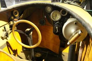 Aero A-10 - dopravní letoun, ČSR / 1922. Pohled do otevřeného prostoru pro letce. Zleva jsou: ovládání přípusti, přepínač magnet, přepínače tlakování a otevírání palivové nádrže, řídící volant, tlakoměr oleje, mechanický otáčkoměr, teploměr oleje, startovací magneto a vzduchová vývěva.