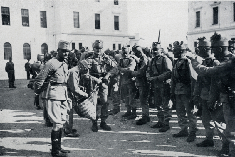 """Rozdílení """"milodarů"""" nastoupeným vojákům. Veřejnost nebyla ke svým vojákům skoupá, naopak si je v době mobilizace a odjezdu na frontu hýčkala nabízením všemožných dobrot na přilepšenou. Foto sbírka VHÚ."""