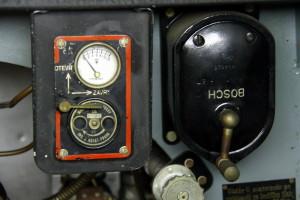 Letov Š-218 - školní letoun, ČSR / 1926. Pohledem do kabiny je vidět přepínač magnet, normální a výšková přípusť motoru, přepínač palivových nádrží, rychloměr, kompas, palubní hodiny, výškoměr, tlakoměr oleje a otáčkoměr. Dále jsou vidět ruční a nožní páky, nastřikování paliva, hasící přístroj Kubát a palubní baterie.