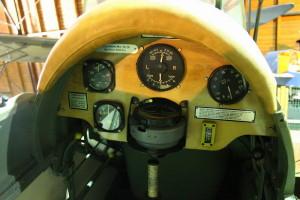 De Havilland DH-82A Tiger Moth Mk. II - turistický a cvičný letoun, Velká Británie / 1931. Pohledem do kabiny je vidět přípusť motoru, otevírání benzínu, rychloměr, výškoměr, zatáčkoměr, vodorovný kompas, otáčkoměr a teploměr oleje. Dále je vidět ruční páka a ovládání slotů.
