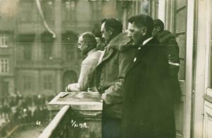 Polní podmaršálek Jan Diviš (ve světlém stejnokroji) spolu se setníkem Rošickým a Josefem Scheinerem (v zákrytu) zdraví z balkonu Vojenského velitelství slavnostní průvod směřující na Bílou horu. Foto sbírka VHÚ.
