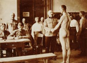 Osudové momenty před lékařskou komisí při takzvaném třídění povolanců. Se vzrůstající poptávkou po vojácích se snižovala zdravotní kritéria a úměrně vzrůstala vynalézavost mužů, jak se službě vyhnout. Jen v taženích roku 1914 ztratilo vojsko podunajské monarchie na 950 000 mužů, z toho 133 000 jich padlo, či zemřelo. V roce 1915 zaznamenalo ztráty ve výši téměř 1,5 milionu mužů, z nichž o život přišlo 177 000.