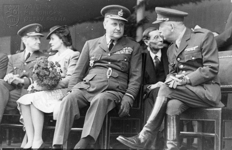 Staroměstské náměstí. Čas 11.00. E. Beneš na tribuně s leteckým maršálem W. Sholto Douglasem, mezi nimi velvyslanec P. Nichols.