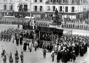 Cognac, 26. prosince 1918. Ministr zahraničních věcí E. Beneš (před tribunou v tmavém kabátě) odevzdává prapor 23. čs. střeleckému pluku.