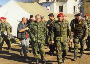 Ministr obrany Vilém Holáň navštívil české vojáky v únoru 1996. Na logistické základně v Bosanské  Krupě ho doprovází velitel praporu plukovník Josef Sedlák.