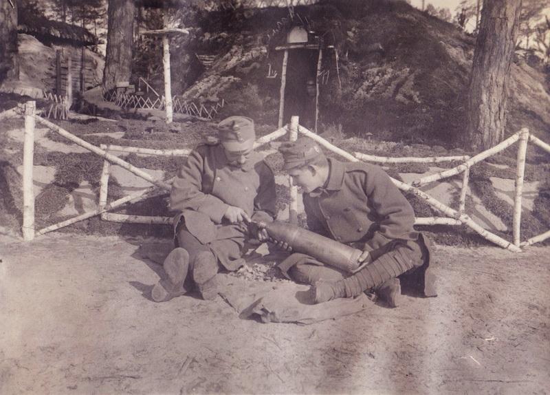 Dvojice vojáků z jičínského c. k. zeměbraneckého pěšího pluku č.11 delaboruje dělostřelecký granát ve snaze získat hliník pro výrobu zákopových prstenů. FOTO: VHÚ Praha