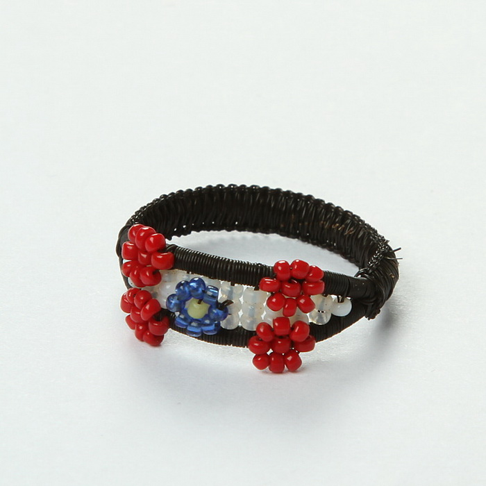 Prsten z černých koňských žíní a korálků s květinovým motivem, vyrobený zřejmě ruskými válečnými zajatci. Podle některých zdrojů se místo koňských žíní mohly používat i vlasy. FOTO: VHÚ Praha