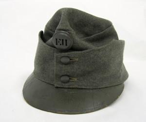 Polní čepice z nového sukna v barvě polní šedi. Kovové části a čelní štítek jsou nalakované krycí barvou, 1915. FOTO: VHÚ