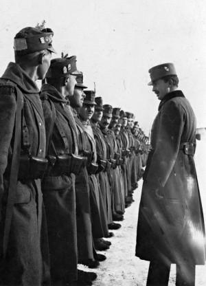 Návštěva císaře Karla I. u vojáků horských jednotek. Dobře patrné jsou identifikační čtverce, řada čepicových odznaků a zimní polní označení – větvičky jehličnanu. FOTO: VHÚ