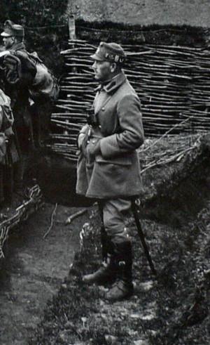 Důstojník ve zkráceném plášti s mnoha čepicovými odznaky na plstěné polní čepici. FOTO: VHÚ