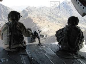 Americký palubní střelec a palubní technik sedí na zadní rampě vrtulníku Boeing CH - 47 Chinook během přeletu českých vojáků ze základny Bagram na předsunutou operační základnu Shank v afghánské provincii Logar. Foto Jindřich Plescher