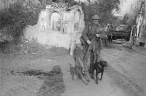 Ernest Brooks: Královský ženista a s kurýrními psy před kapličkou u cesty, prosinec 1917. FOTO: IWM