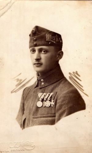 Desátník 61. uherského pěšího pluku s čepicí zdobenou odznaky, umístěnými nepředpisově na levé straně. Rozeznatelné jsou odznaky pušky zkřížené s bajonetem, odznak s číslem pluku 61 a odznak 4. Vánoc v poli (1917). Na hrudi směrem od zapínání blůzy vyznamenání:  Stříbrná a patrně bronzová Medaile za statečnost (Tapferkeitsmedaille), Karlův vojenský kříž (Karl-Truppenkreuz) a Vojenský služební odznak (Militär-Dienstzeichen der k. u. k. Armee) pro mužstvo a poddůstojníky.  FOTO: VHÚ.