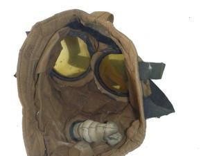 Britská ochranná maska SBR. Jde o dvoucestnou ochrannou masku s šitou látkovou lícnicí z pogumovaného hedvábí a pětibodovou upínací soustavou s gumotextilními pásky. Maska ve velikosti 3.  Foto: VHÚ