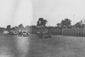 Velitel oddílu polního četnictva Československé samostatné obrněné brigády, major František Divoký, vede kolonu vozidel prezidenta republiky při přehlídce brigády v Praze na Vypichu 30. května 1945.