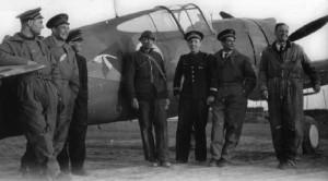 """Letiště Suippes ve Francii, 12. května 1940. Po dalším úspěšném boji, tentokrát se střemhlavými Stukami, z nichž dvě sestřelil jistě a dvě pravděpodobně. Zleva esa 1. letky GC I/5 čet. G. Muselli, rt. L. Vuillemain, rtm. F. Peřina, neznámý, kpt. J. Accart (velitel letky), npor. E. Marin la Meslée (zástupce velitele letky) a por. M. Rouquette. Za nimi Accartův Curtiss H-75 No 151 (""""bílá 1"""") se znakem letky, letícím čápem."""