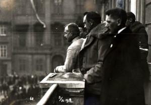 Polní podmaršálek Jan Diviš (ve světlém stejnokroji) spolu se setníkem Rošickým a Josefem Scheinerem (v zákrytu) zdraví z balkonu Vojenského velitelství slavnostní průvod směřující 3. listopadu 1918 na Bílou horu. (VHÚ Praha)