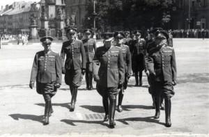Důstojníci Vládního vojska na Velkém náměstí v Hradci Králové kráčejí na manifestaci dokazující věrnost nacistickým okupantům, polovina roku 1942