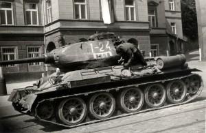 Člen filmového štábu na sovětském tanku T-34-85, jakoby zasaženém na Klárově při natáčení filmu Osvobození Prahy