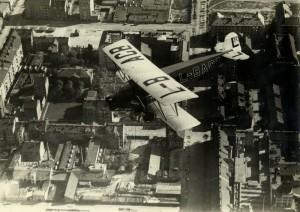 Československý dopravní letoun Aero A-38 v letu nad městem, patrně počátek 30. let