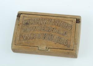 Dřevěnou krabičku na tabák vyrobil v rakousko-uherském zajateckém táboře v Terezíně příslušník ruské armády polské národnosti. Tělo tabatěrky je vyrobeno z jediného kusu dřeva, ke kterému je přiděláno víčko s vyřezávaným nápisem. Tabatěrka zřejmě sloužila jako obchodní artikl při kontaktech s rakouskými strážci a místním obyvatelstvem. Rozměry krabičky jsou 10,8 x 7,2 x 3 cm.