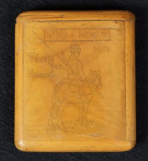 Dřevěné pouzdro na cigarety s jezdeckým motivem a do strany vysunovacím víkem. Na druhé straně je rytina jezdce s furažkou a šaškou. Zřejmě práce rakousko-uherských zajatců v Rusku. Rozměry pouzdra jsou 13 x 11 x 2,2 cm.