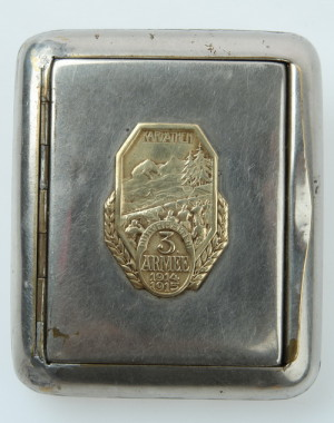 Tabatěrka z běžné tovární produkce s přiletovaným čepicovým odznakem třetí armády, odkazující na obranné boje v Karpatech v zimě 1914–1915. Rozměry tabatěrky jsou 8,5 x 7 x 1,5 cm.