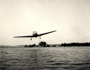 Československý školní a sportovní letoun Zlín Z-22 Junák v letu nad rybníkem, konec 40. let