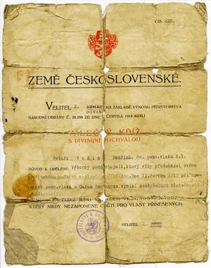 Omšelý dekret k Československému Válečnému kříži 1914-1918 s divizní pochvalou od plukovníka Šnejdárka. Četař Bedřich Vašin z osádky obrněného vlaku č. 1 (původně IIa) si vyznamenání vysloužil za bojovou akci z 12. června 1919 u Hronské Breznice. Obrněný vlak č. IIa, jemuž dočasně scházel dělový vůz, vyřadil z boje maďarský protějšek neotřelým způsobem – poslal proti němu po svažující se trati svůj předběžný plošinový vůz naložený kolejnicemi a pražci. (VHÚ Praha)