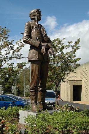 """Socha velitele 11. skupiny Air Vice-Marshala Keithe Parka (1892–1975) stojí – možná tak trochu nedůstojně – u parkoviště návštěvnického centra. Je kopií bronzové sochy, která byla slavnostně odhalena 15. září 2010 u příležitosti 70. výročí Bitvy o Británii na londýnském Waterloo Place. Autorem sochy """"obránce Londýna"""", jak je Park často nazýván, byl Leslie Johnson. FOTO: Jaroslav Beránek"""