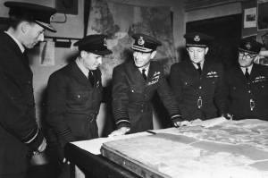 Air Vice Marshal Ralph Cochrane, Wing Commander Guy Gibson, král Jiří VI. a Group Captain John Whitworth diskutují 27. května 1943 o operaci CHASTISE na velitelství 5. skupiny Bomber Command v Granthamu. FOTO: RAF Museum